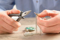 Creating or fixing jewelry man repairing silver chain with pliers Stock Image
