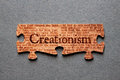 Creationism jigsaw matched the word against background of genesis text printed on pieces Royalty Free Stock Images