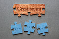 Creationism matched and evolution mismatched jigsaw against background of genesis text printed on pieces with against background Royalty Free Stock Image