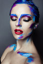 Creative art makeup of a young girl with blue eyes strokes paint on her face and hair Royalty Free Stock Photography