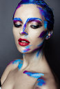 Creative art makeup of a young girl with blue eyes strokes paint on her face and hair Royalty Free Stock Photo