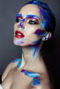 Creative art makeup of a young girl with blue eyes strokes paint on her face and hair Royalty Free Stock Photos