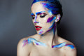 Creative art makeup of a young girl with blue eyes strokes paint on her face and hair Stock Photography