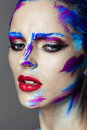 Creative art makeup of a young girl with blue eyes strokes paint on her face and hair Stock Images