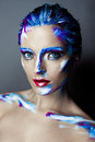 Creative art makeup of a young girl with blue eyes strokes paint on her face and hair Stock Photo