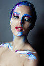 Creative art makeup of a young girl with blue eyes strokes paint on her face and hair Stock Photos