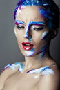 Creative art makeup of a young girl with blue eyes strokes paint on her face and hair Stock Image