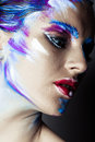 Creative art makeup of a young girl with blue eyes strokes paint on her face and hair Royalty Free Stock Images