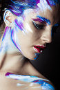 Creative art makeup of a young girl with blue eyes strokes paint on her face and hair Royalty Free Stock Image