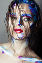 Creative art makeup of a young girl with blue eyes strokes paint on her face and hair wet hair on her face Royalty Free Stock Images