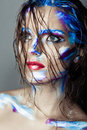 Creative art makeup of a young girl with blue eyes strokes paint on her face and hair wet hair on her face Royalty Free Stock Photo