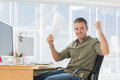 Creative business employee raising arms in a modern office Stock Photos