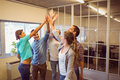 Creative business team raising their hands at the office Stock Image