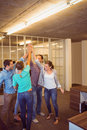 Creative business team raising their hands at the office Royalty Free Stock Photo