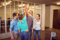 Creative business team raising their hands at the office Royalty Free Stock Photos