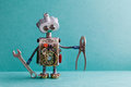 Creative design electrician robot with hand wrench pliers. Funny toy mechanic character lamp bulb eyes head, electric Royalty Free Stock Photo