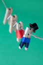 Creative design peg characters and clothesline. Man in suit, woman red dress. wooden clothespins on green background
