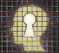 Creative freedom key with a human head light glowing on a brick wall through a prison cage opened with a keyhole shape as a Royalty Free Stock Images