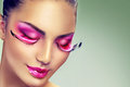 Creative holiday makeup with false long purple eyelashes