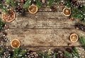 Creative layout frame made of Christmas fir branches, spruce, slices of orange, pine cones, snowflakes on wooden background Royalty Free Stock Photo