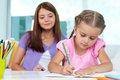 Creative leisure cute little girl drawing with her mother on background Royalty Free Stock Image