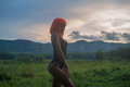 Creative look of sexy woman in orange wig isolated on green field over sunset