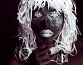 Creative makeup like Ethiopian mask, white pattern on black face close up, halloween horror Royalty Free Stock Photo