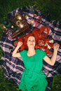 Creative portrait of beautiful redhead woman lying on grass among romantic decoration Stock Images