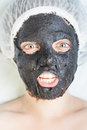 Creative woman in spa salon with black mud face mask Royalty Free Stock Photo