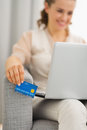 Credit card in hand of woman using laptop closeup on Stock Photos