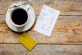Credit card for paying, coffee and check on cafe wooden desk background top view mock up Royalty Free Stock Photo