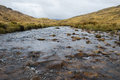 Creek in the highlands of scotland with rain clouds Royalty Free Stock Photo