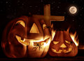 Creepy halloween night glowing carved pumpkin with scary horrible spiders cross and burning flame on the graveyard in full moon Stock Photo