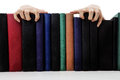 Creepy hand hands coming over books on a bookshelf Royalty Free Stock Images