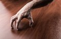 Creepy hand on the wooden table Royalty Free Stock Image