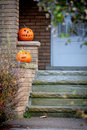 Creepy house and halloween pair of pumpkins carved for sitting on steps of a image orientation is vertical there is copy space Royalty Free Stock Photo