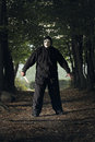 Creepy masked killer with knife in the woods halloween and horror concept Stock Photo