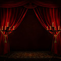 Creepy room an old with red curtains and two chandeliers that illuminate Stock Photos