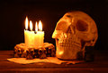 Creepy skull with candles and poison human on the wooden table in the darkness Stock Photo