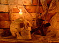 Creepy skull with cross human wooden and burning candle Royalty Free Stock Photo
