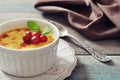 The creme brulee in ceramic baking mold with mint and berries on wooden table Royalty Free Stock Photos