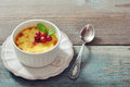 The creme brulee in ceramic baking mold with mint and berries on wooden table Royalty Free Stock Image