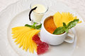 Creme brulee classic with mango sauce and mint twig Royalty Free Stock Images