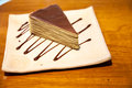 Crepe cake in square japanese style dish on the wood table with zigzag chocolate sauce Royalty Free Stock Photography