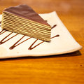 Crepe cake in square japanese style dish on the wood table with zigzag chocolate sauce Royalty Free Stock Photo