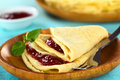 Crepe with jam fresh homemade folded filled strawberry on wooden plate selective focus focus on the front of the lower layer of Royalty Free Stock Photography