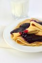 Crepes with confiture and glass of milk on background Stock Photo