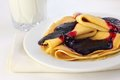 Crepes with confiture and glass of milk on background Royalty Free Stock Image