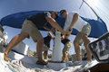 Crew members operating windlass on yacht low angle view of Stock Image