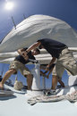 Crew members operating windlass on yacht low angle view of Stock Photos